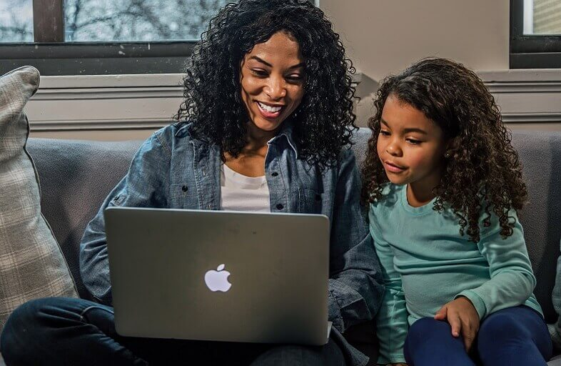 black female and daughter working on Apple computer in living room