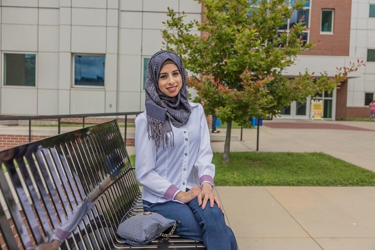 female student sitting outside on bench in front of campus building